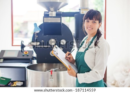 Woman working on coffee factory standing near the roasting machine - stock photo