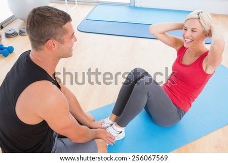Woman working on exercise mat with her trainer in fitness studio - stock photo