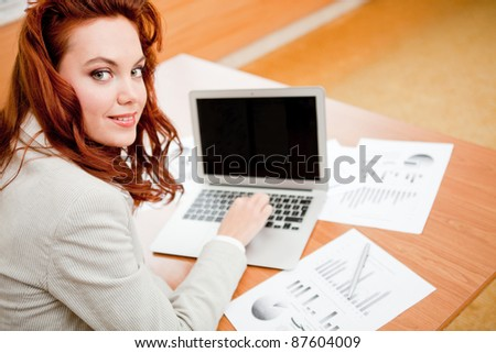 Woman working on her online business with a laptop computer - stock photo