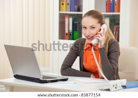 Woman working on her workplace calling on phone - stock photo