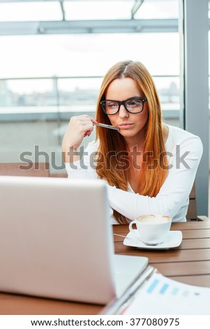 Woman working on laptop at cafeteria - stock photo