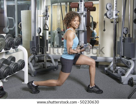 Woman working out doing lunges and curls with weights in a gym - stock photo