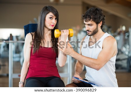 Woman working out in a gym while her personal trainer looks at the execution - stock photo