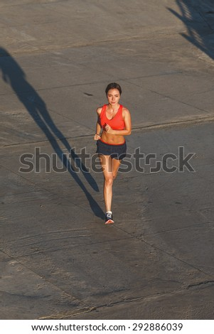woman working out in an urban setting, running along stone wall, top view