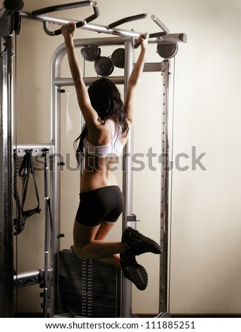 Woman working out in gym - pull ups. Image cross processed, contrasty,  dark grainy image. - stock photo