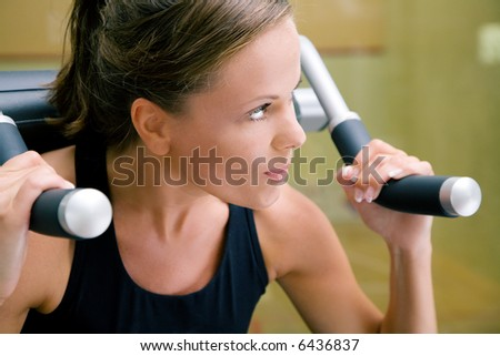 Woman working out lifting weights in a gym - stock photo