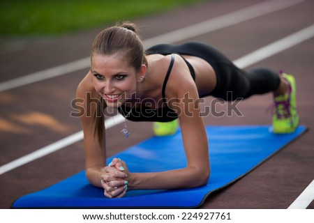 Woman working out on athlete track on summer afternoon - stock photo