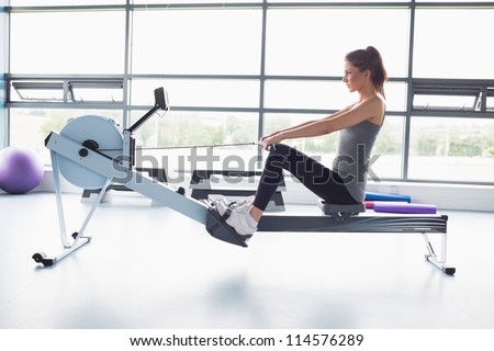 Woman working out on row machine in gym - stock photo