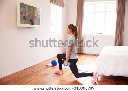 Woman Working Out To Fitness DVD On TV In Bedroom