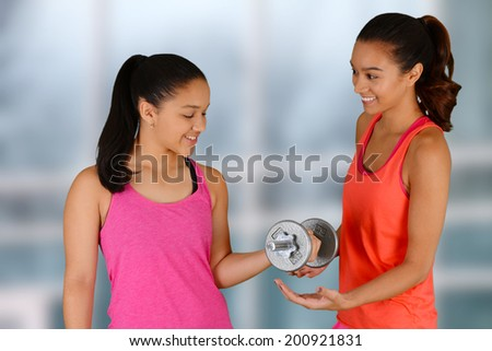 Woman working out while at the gym with a personal trainer - stock photo