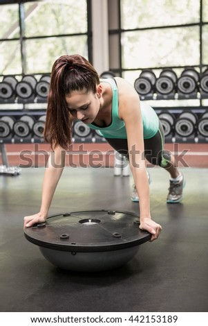 Woman working out with bosu ball at gym - stock photo