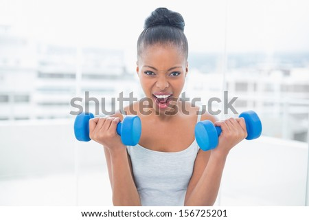 Woman working out with dumbbells at home - stock photo