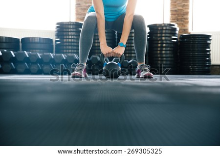Woman working out with kettle ball at gym - stock photo