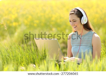 Woman working with a laptop and headphones in the middle of a a field in summer - stock photo