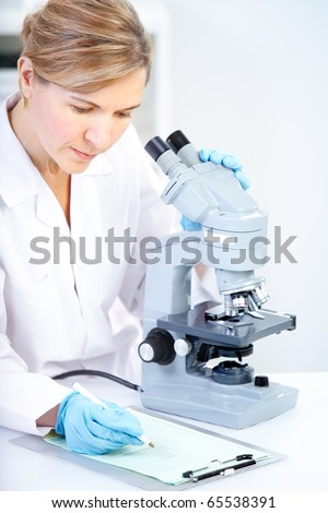 Woman working with a microscope in a lab - stock photo