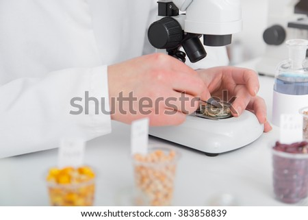 Woman working with a microscope in a lab.Toning image - stock photo
