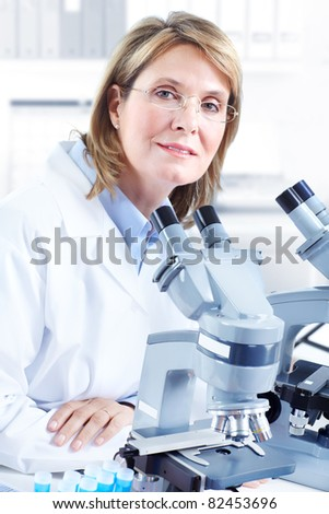 Woman working with a microscope in laboratory.