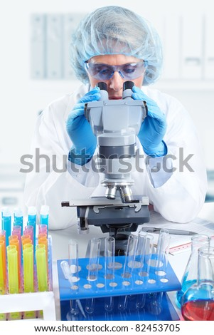 Woman working with a microscope in laboratory. - stock photo