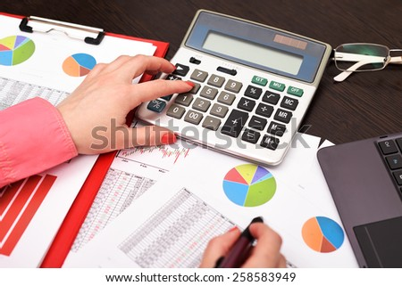 woman working with calculator in office - stock photo