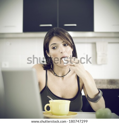 woman working with her laptop while eating her breakfast  - stock photo