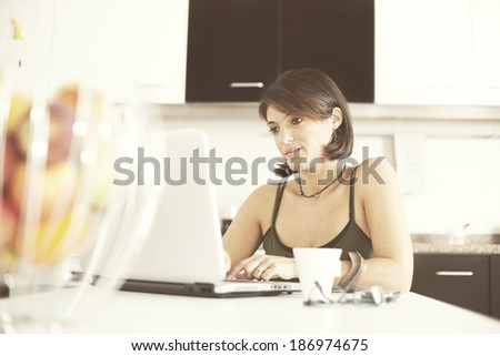 woman working with her laptop while eating her breakfast (selective focus with shallow DOF) - stock photo