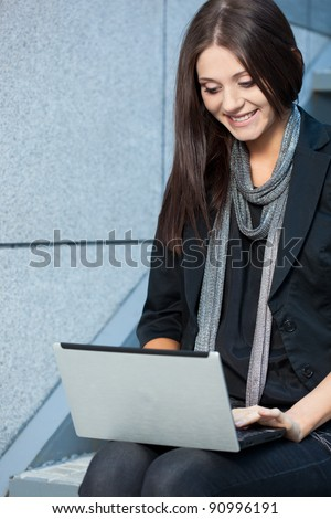 woman working with laptop near wall