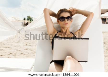 Woman working with laptop on the beach - stock photo
