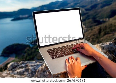 Woman working with laptop on the top of mountain with beautiful landscape on background. Blogging concept - stock photo