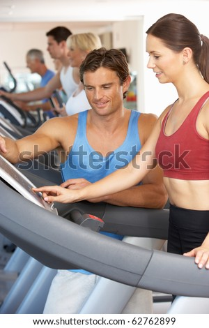 Woman Working With Personal Trainer On Running Machine In Gym