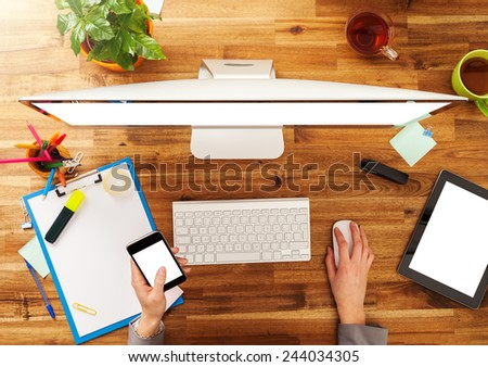 Woman working with smart phone and pc placed on wooden desk. Shot from aerial view - stock photo