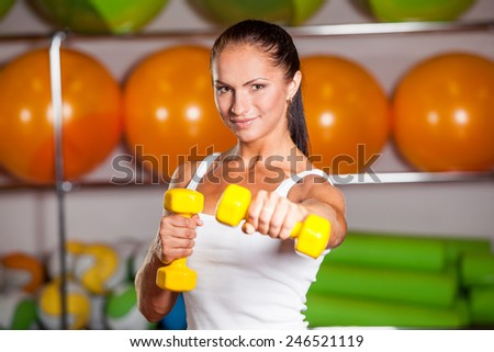 Woman workout with dumbbell in gym, biceps exercise closeup - stock photo