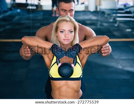 Woman workout with kettle ball and coach in gym - stock photo