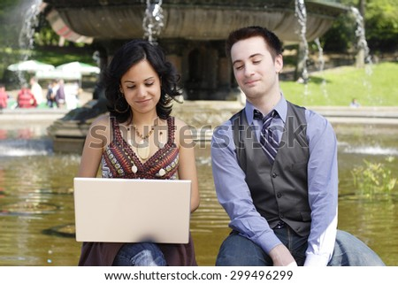 Woman works on laptop as man looks at the screen. - stock photo