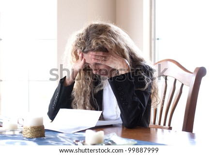 woman worried about bills and debt and foreclosure with headache - stock photo