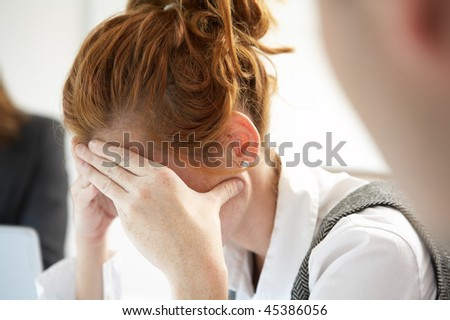 Woman worried in business meeting - stock photo