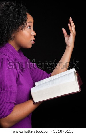 Woman worshipping God holding bible