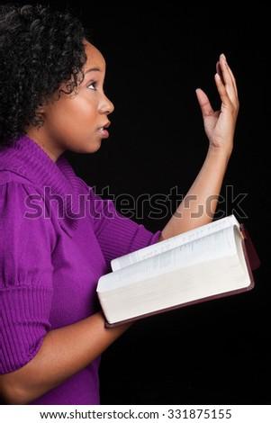Woman worshipping God holding bible - stock photo