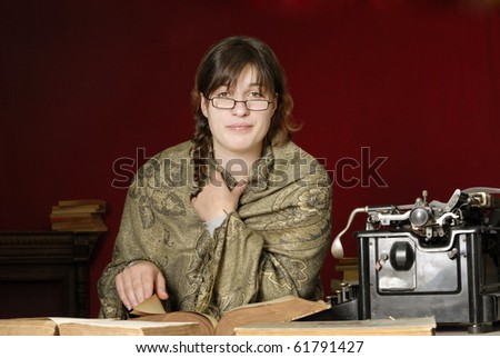 woman wrapped in a green shawl glasses reading an old book next to an antique typewriter, on dark red background - stock photo