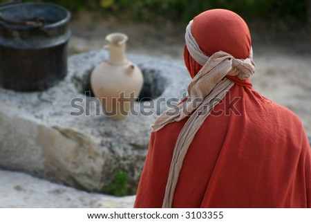 Woman wrapped in cloth sits in front of a 1st century well - stock photo