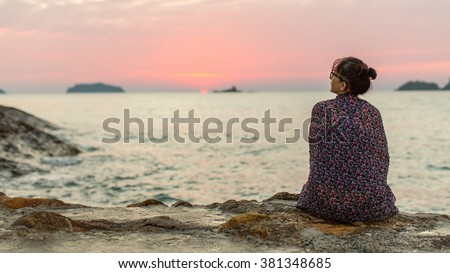 Woman wrapped in plaid sits lonely on the coast. - stock photo