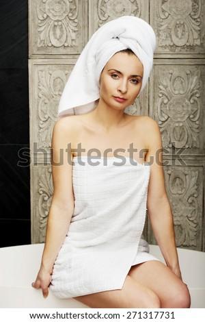 Woman wrapped in towel sitting on bathtub in bathroom. - stock photo