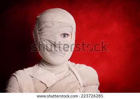 woman wrapped up with bandages as a mummy halloween costume - stock photo