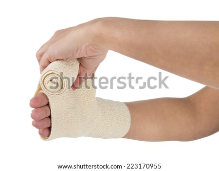 Woman wrapping her hand with a bandage on a white background    - stock photo