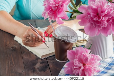 Woman write in notebook, flowers on table, Vacation work