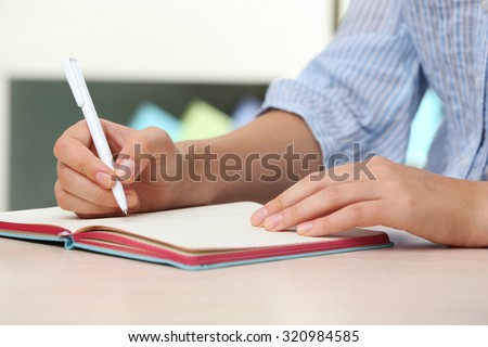 Woman write on notebook on workplace close up - stock photo