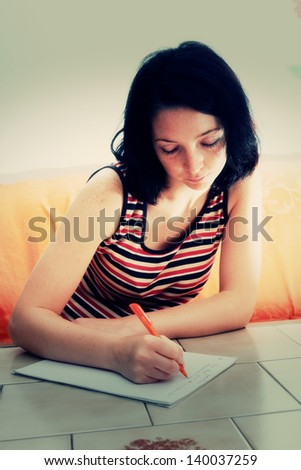 woman writes a letter to on paper