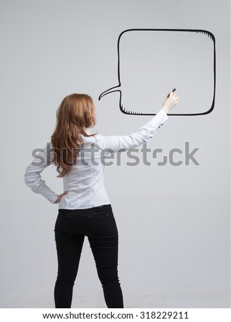 woman writes in a painted speech bubble - stock photo