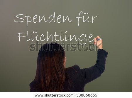 Woman writes the german words Donations for Refugees / Donations for Refugees - stock photo