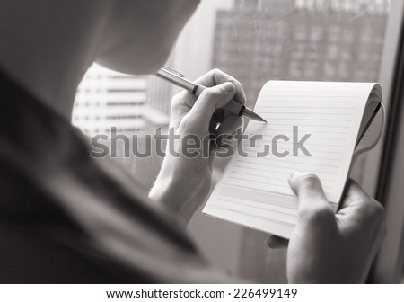 Woman writing a letter, notes. Close up view of her hand and the document - stock photo
