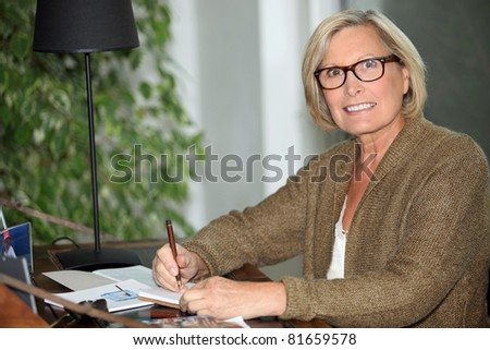 Woman writing at her desk - stock photo